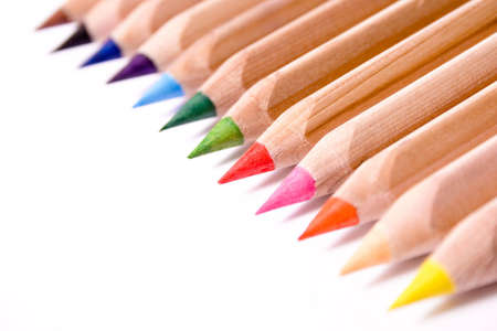 Row of colored pencils on white background.