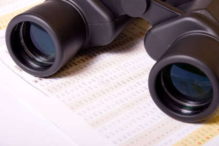 Binoculars on table with financial figures