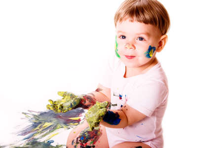 Child showing her palms colored with yellow paint.