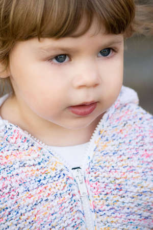 Portrait of 2 years old girl in white knitted jacket.