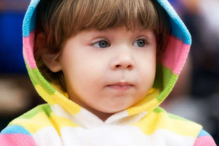 Cute 2 year old girl in casual hood jacket looking after her mother.