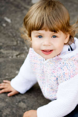 Portrait of 2 years old girl in casual white cardigan. Stock Photo