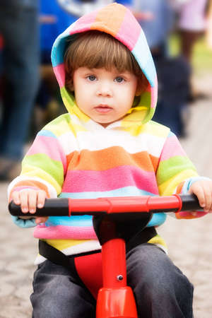 Little girl in colorful hood jacket driving red scooter. Stock Photo