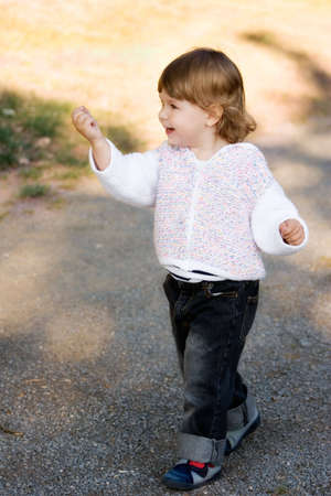 Beautiful little girl in white jacket and jeans showing something she just found.
