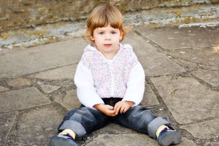 Little girl in knitted casual coat sitting on the ground.