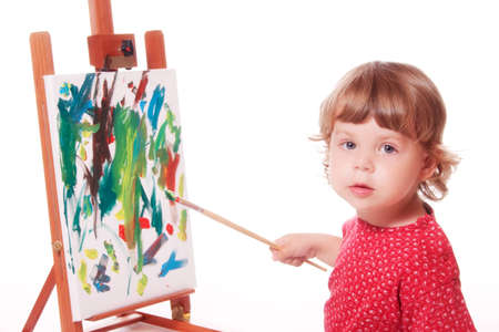 artwork: 2 year old girl in profile, painting on an easel. Isolated on a white studio background. Stock Photo