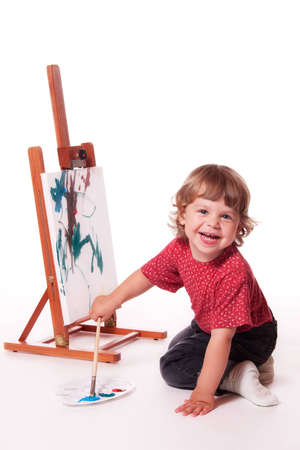 messy kids: 2 year old girl in profile, painting on an easel with palette. Isolated on a white studio background.