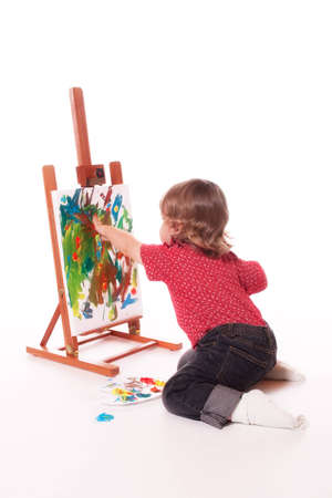 2 year old girl in profile, painting on an easel with fingers. Isolated on a white studio background.