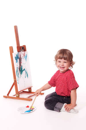 2 year old girl in profile, painting on an easel. Isolated on a white studio background. Standard-Bild