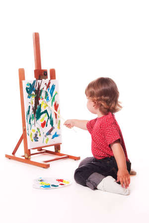 engrossed: 2 year old girl in profile, painting on an easel with paintbrush. Isolated on a white studio background. Stock Photo