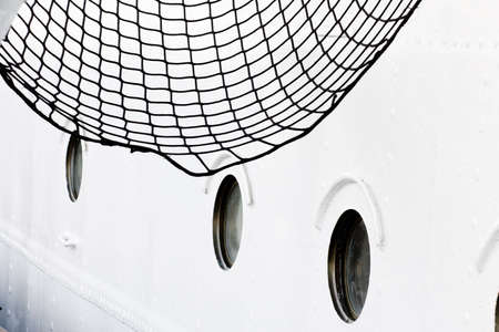 Fragment of the sail ship board with net and portholes. Taken on the old German sail ship. Stralsund, Baltic Sea.