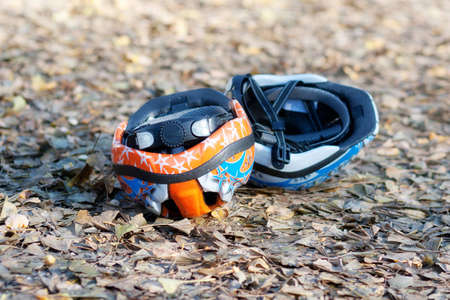 Two cycling helmets on the ground. Outdoor cycling in park with kids. A weekend in November.  Stock Photo
