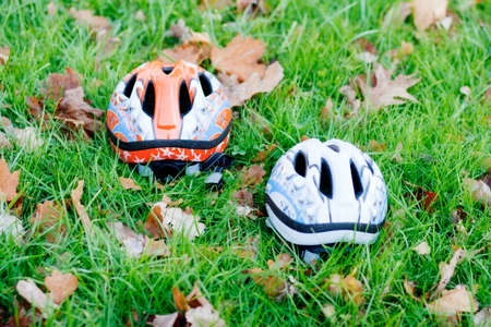 Two cycling helmets in the grass. Outdoor cycling in park with kids. A weekend in November.