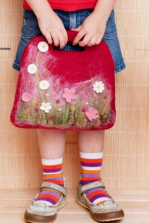 Handmade felt bag in the girls hands. Stock Photo