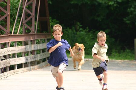 kids playing outside: Boys Running with Dog Stock Photo