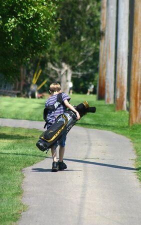 Boy llevar bolsa de golf  Foto de archivo - 527260