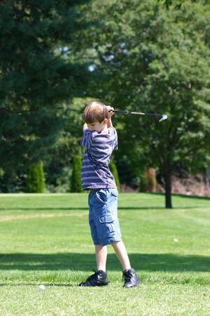 Boy Swinging Golf Club  Foto de archivo - 527192