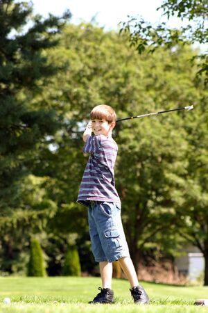 teen golf: Muchacho Que sonr�e Jugando Golf Foto de archivo