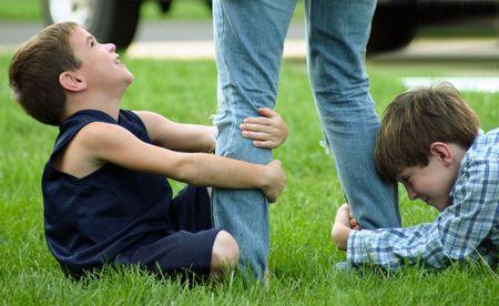 Niños tirando en las piernas  Foto de archivo - 561964