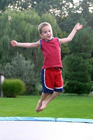 ni�o saltando: Boy saltar en cama el�stica  Foto de archivo