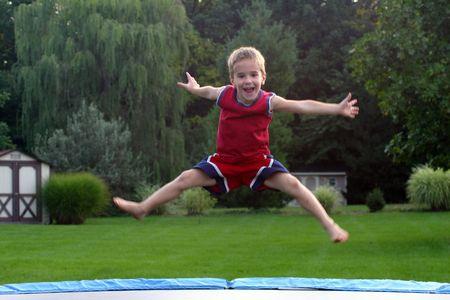 ni�o saltando: Boy de saltos de trampol�n en  Foto de archivo