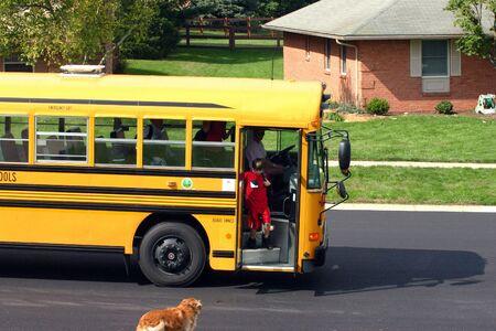 Boy Getting off School Bus Greeting Dog Stock Photo - 561910