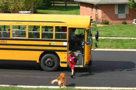 Boy Getting off School Bus and Dog Greeting Stock Photo - 561911