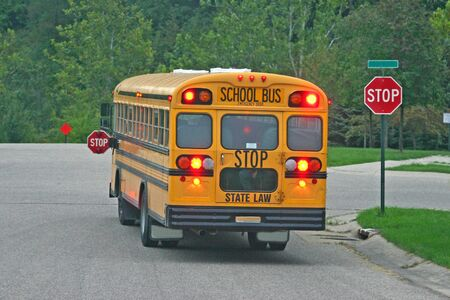 school buses: School Bus Braking at Stop Sign Stock Photo