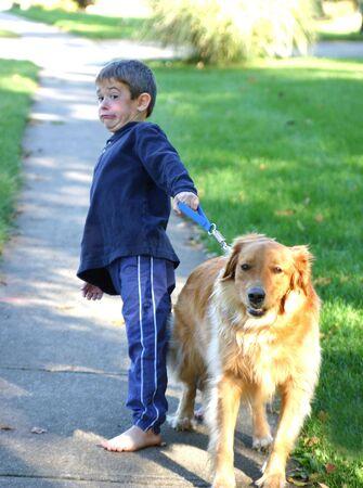 Boy Holding Back Dog From Running photo