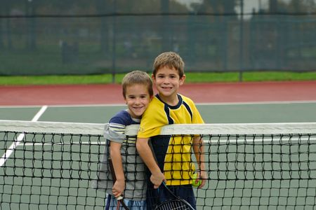 hermanos jugando: Dos ni�os jugando tenis