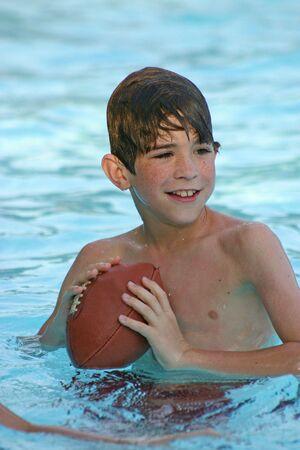 jugando futbol: Boy jugar al f�tbol en la piscina  Foto de archivo