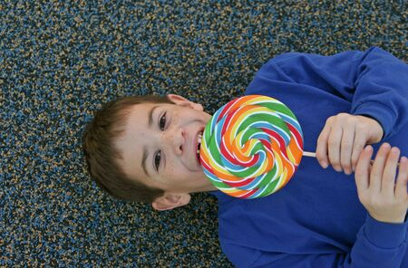 eating: Boy Laying Down Eating a Lollipop