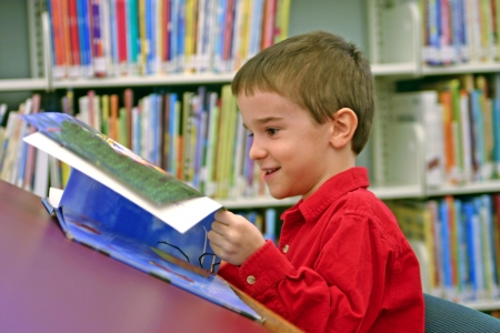 boy reading book at the library photo