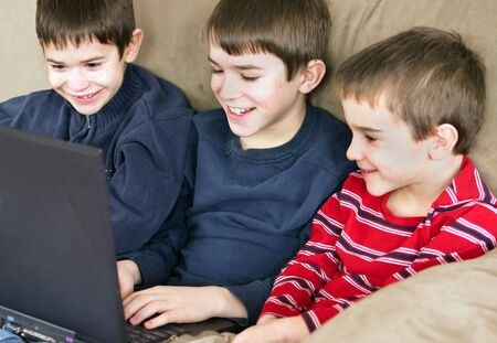 teens playing: A group of three boys playing on computer together