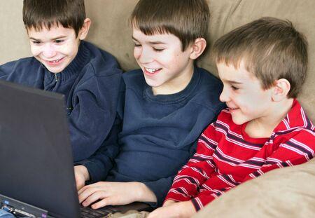 ni�os jugando videojuegos: Un grupo de tres muchachos que juegan en la computadora junto  Foto de archivo