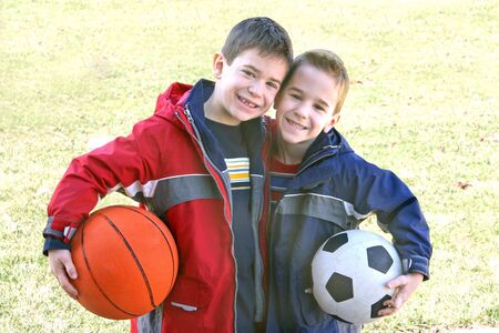 Two young boys holding sports balls under their arms