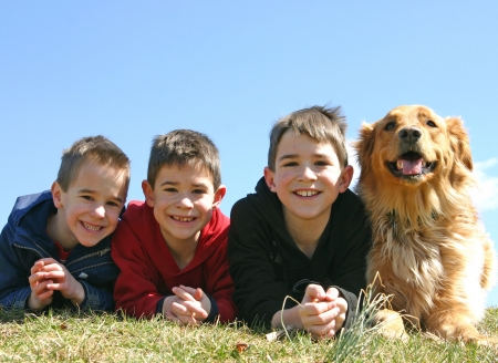 A dog smiling with three young boys Stock Photo