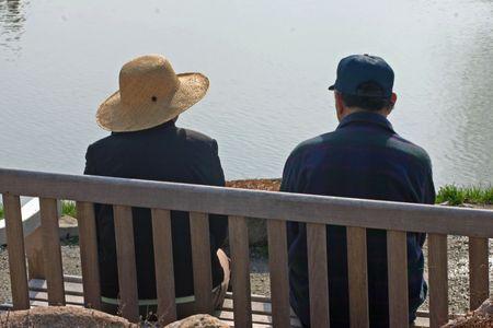bench park: Un anciano y la mujer sentada en una banca del parque Foto de archivo