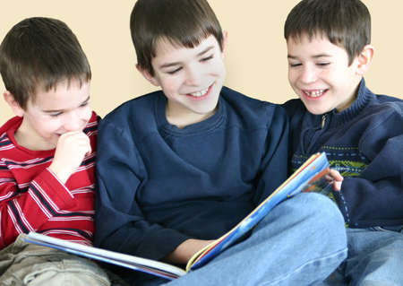 Three Boys reading a funny book together Stock Photo