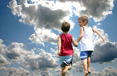 Two boys holding hands running up to heaven Stock Photo