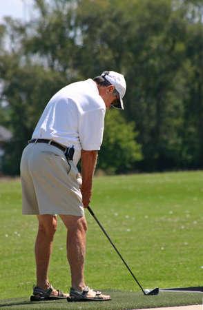 An elderly man practicing his golfing game photo