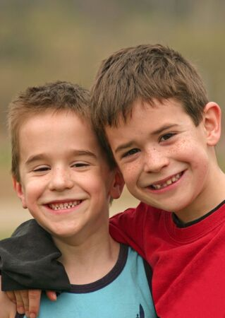 Two Brothers smiling with their arms around each other