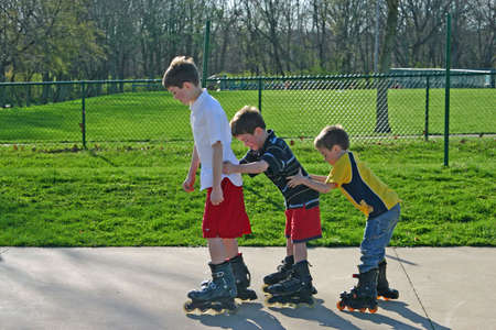 blading: Kids Roller-Blading in a Row Stock Photo