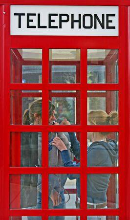 cabina telefonica: Las ni�as en una cabina telef�nica y hablar Laughing