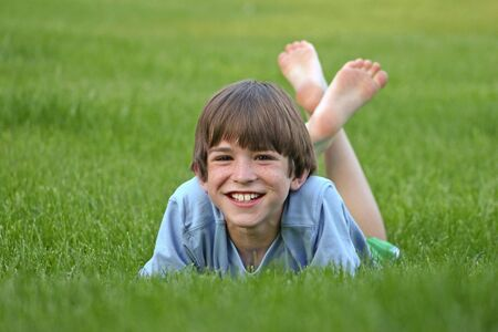 Boy with big smile laying in grass 스톡 콘텐츠
