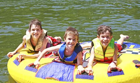 yellow boats: Three Boys Tubing Stock Photo