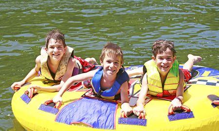 tubing: Three Boys Tubing Stock Photo