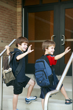 first day: Two Boys Going into School Stock Photo