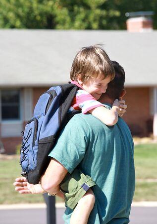 ni�os saliendo de la escuela: Chico poco despu�s de largos abrazos pap� D�a en la Escuela Foto de archivo