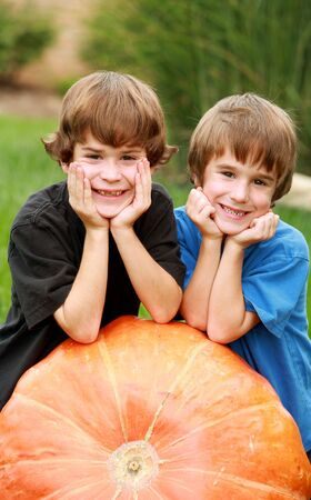 Two Boys Resting on a Pumpkin Stock Photo - 1815676